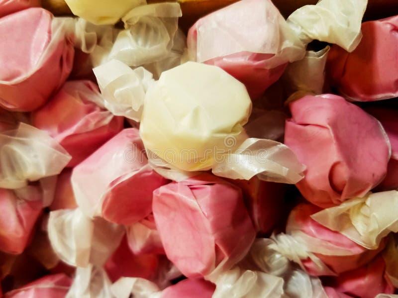 可口看起来的被包裹的桃红色和黄色奶糖糖果-选择聚焦 免版税图库摄影