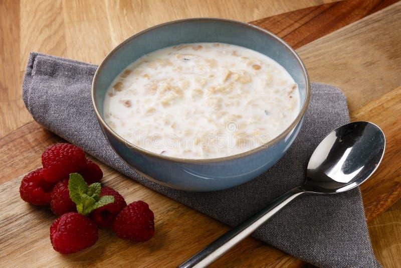 可口碗在一个木板的粥和raspberrys射击有餐巾和匙子的 库存图片