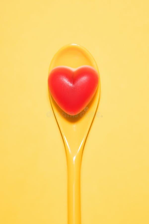 可口糖果顶视图在红色心脏形状的在匙子的和 库存图片