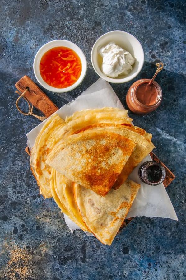 可口绉纱俄式薄煎饼用在一个木板的被分类的调味汁 免版税库存图片