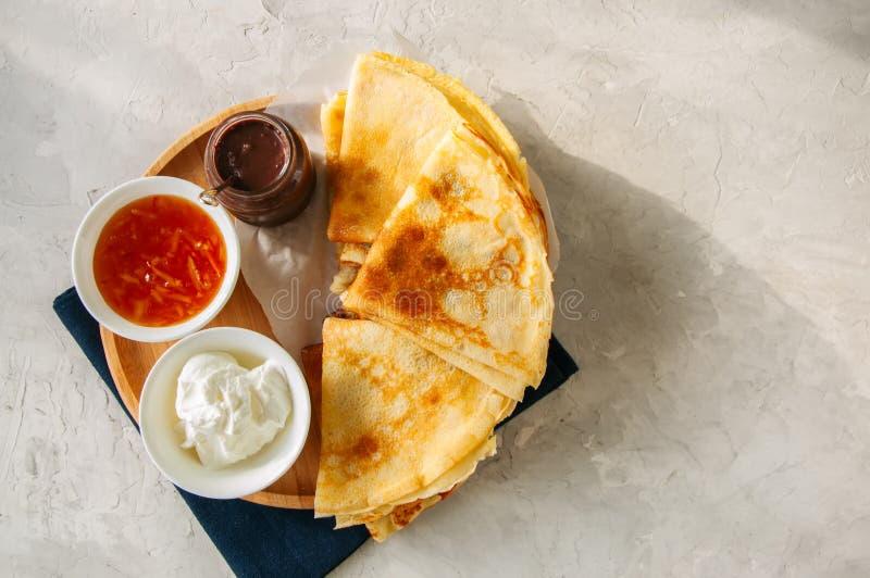 可口绉纱俄式薄煎饼用在一个木板的被分类的调味汁 免版税图库摄影