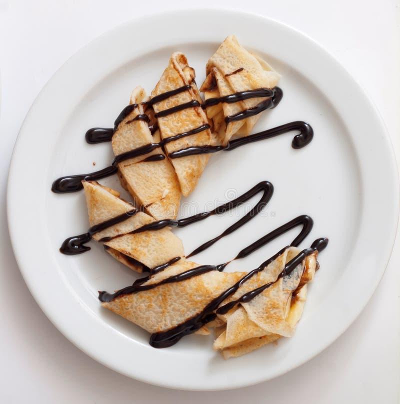 可口绉纱板材滚动用新鲜水果和巧克力在一块白色板材 图库摄影