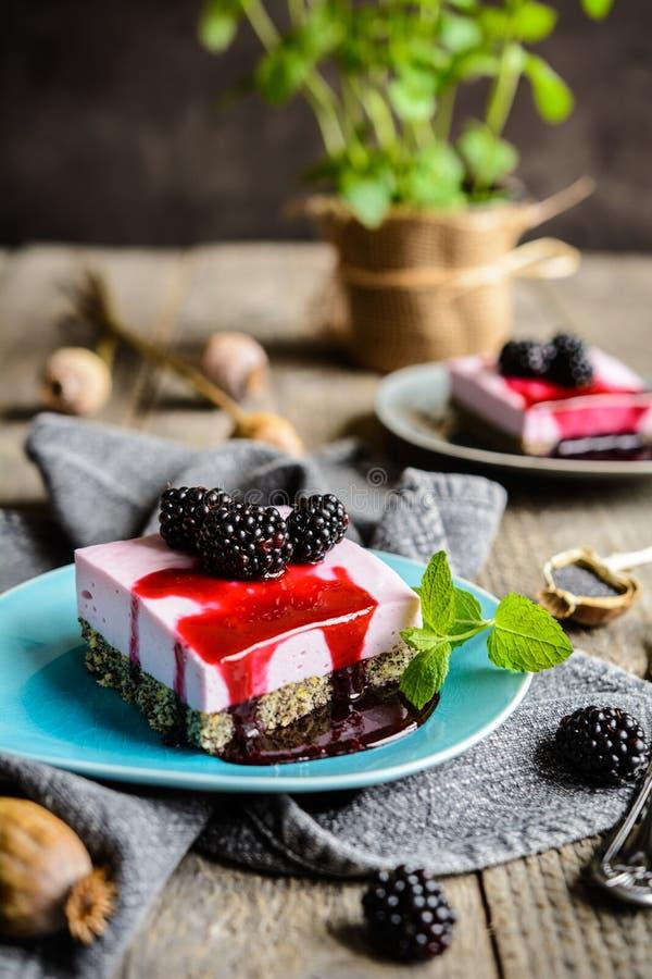 可口罂粟种子和黑莓乳酪蛋糕冠上了用黑莓调味汁 免版税图库摄影