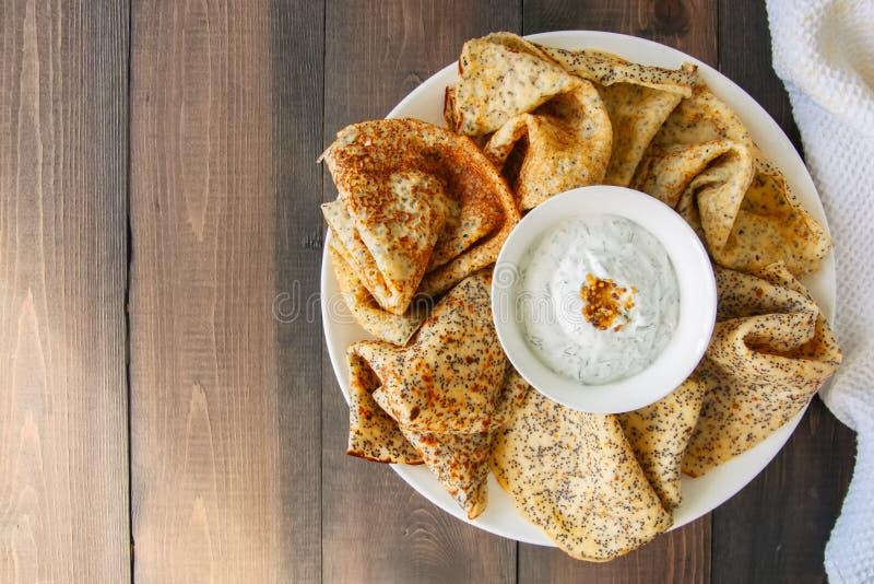 可口罂粟种子弄皱俄式薄煎饼和酸性稀奶油调味汁与d 库存照片