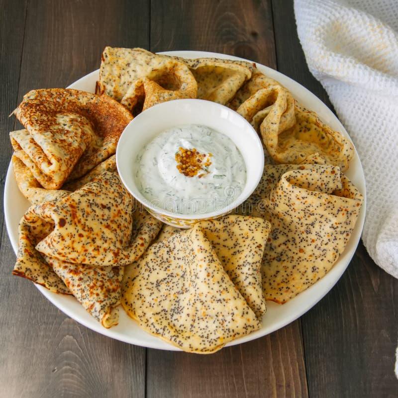 可口罂粟种子弄皱俄式薄煎饼和酸性稀奶油调味汁与d 免版税库存照片