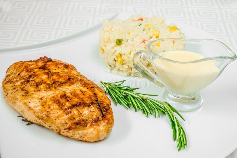 可口肉炸肉排、草本、米用玉米和调味汁,在一块白色板材 水平的框架 库存图片