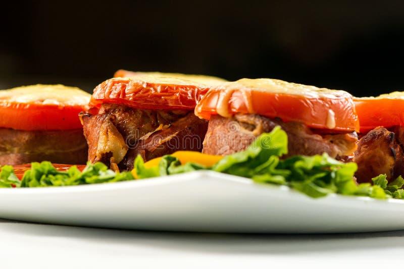 可口肉饼用菠菜、乳酪和蕃茄在板材在白色背景 免版税图库摄影