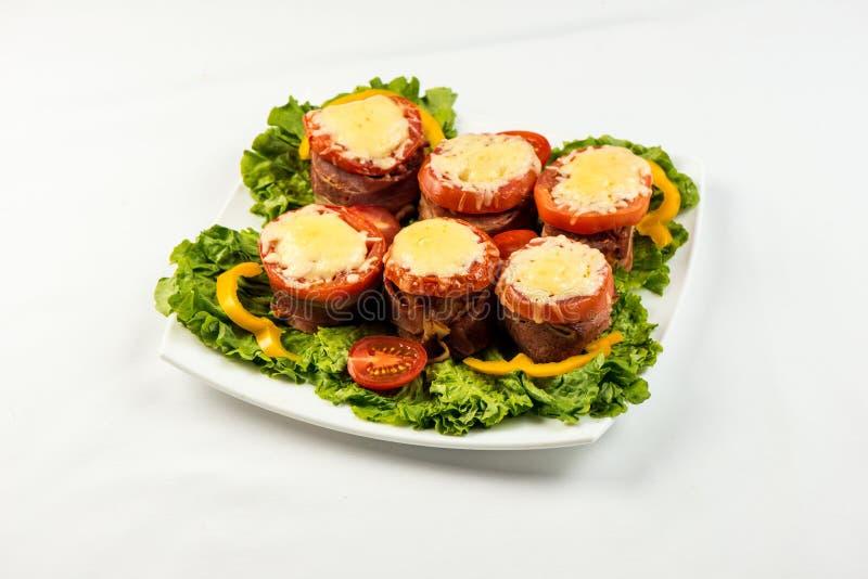 可口肉饼用菠菜、乳酪和蕃茄在板材在白色背景 图库摄影