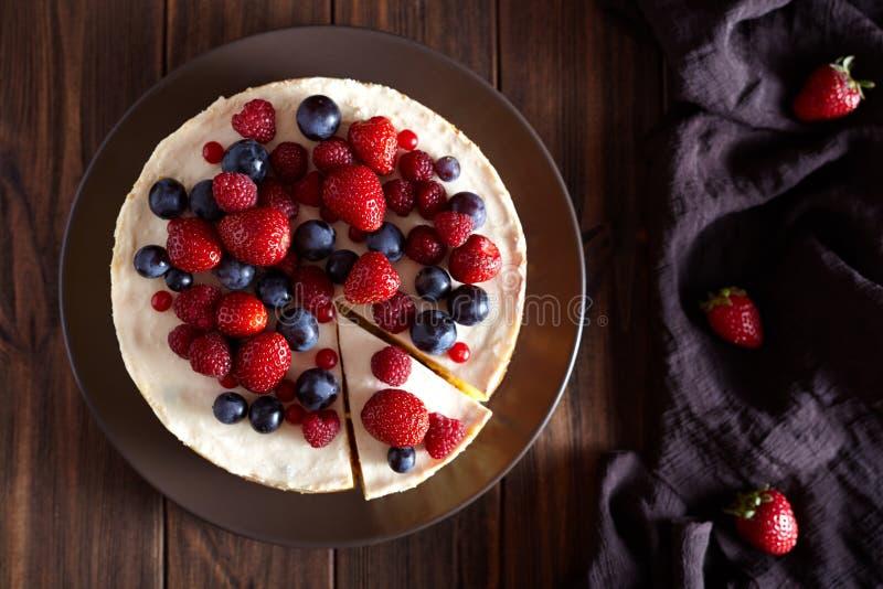 可口自创乳脂状的mascarpone纽约乳酪蛋糕用在黑暗的木桌上的莓果 顶面viev 库存图片