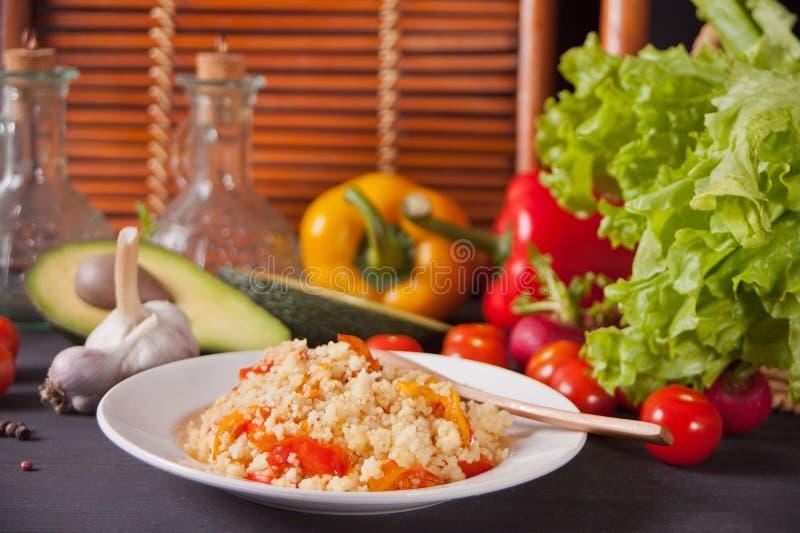 可口自创素食蒸丸子用蕃茄、红萝卜、胡椒和新鲜的蓬蒿在黑暗的厨房用桌上与菜 免版税库存图片