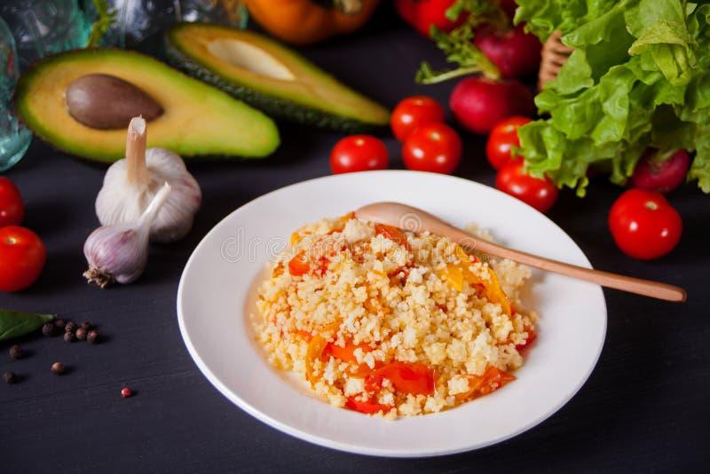 可口自创素食蒸丸子用蕃茄、红萝卜、胡椒和新鲜的蓬蒿在黑暗的厨房用桌上与菜 免版税图库摄影
