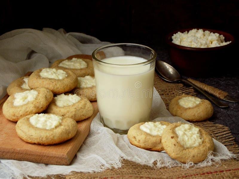 可口自创饼干 脆饼用乳脂干酪曲奇饼和杯在黑暗的背景的牛奶 免版税库存图片