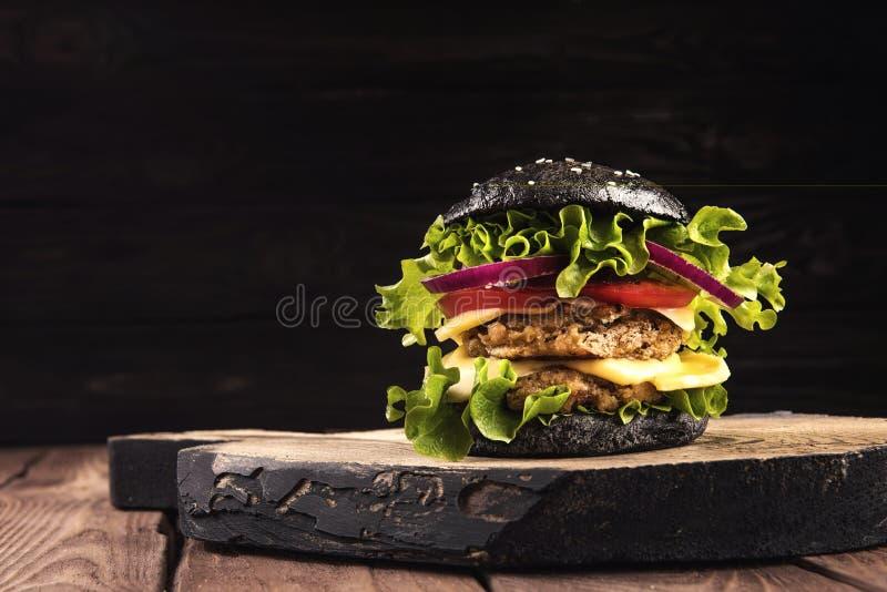 可口自创素食主义者黑色汉堡用两鸡豆炸肉排、蕃茄、乳酪、葱和沙拉在木桌上,黑暗 免版税库存照片