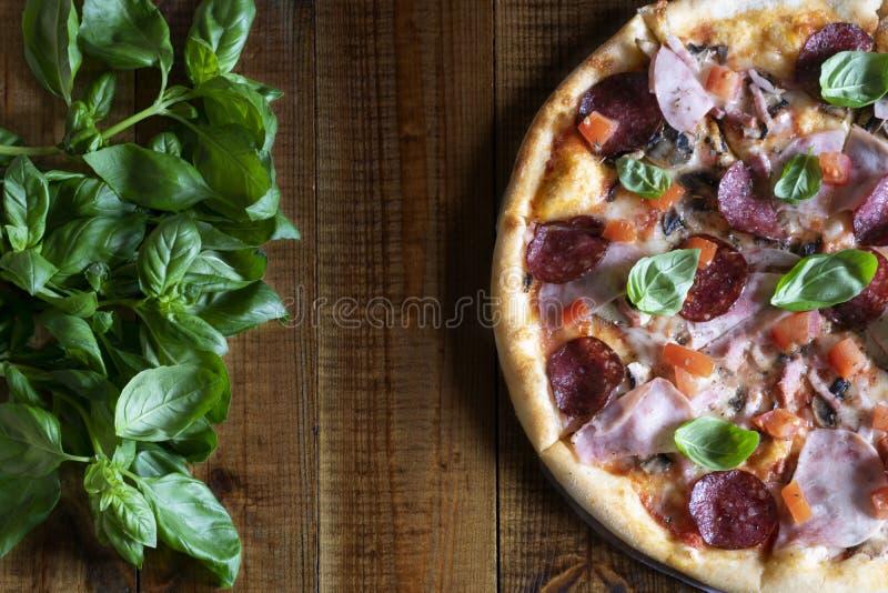 可口芬芳比萨用蘑菇、蒜味咸腊肠、火腿、蕃茄、无盐干酪和新鲜的蓬蒿在一张木桌上 免版税库存照片
