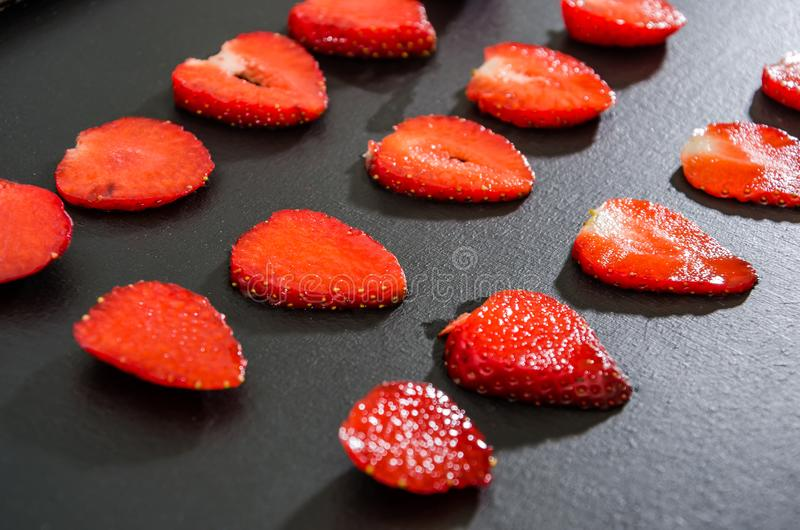 可口草莓,裁减成在黑背景的切片 背景用草莓 图库摄影