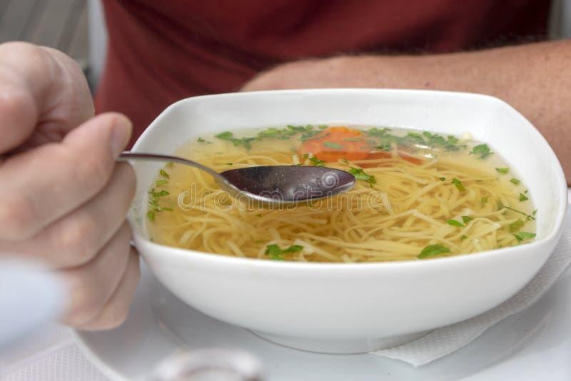 可口菜汤用在白色碗,在手中不锈钢匙子的面条,立即可食 免版税图库摄影