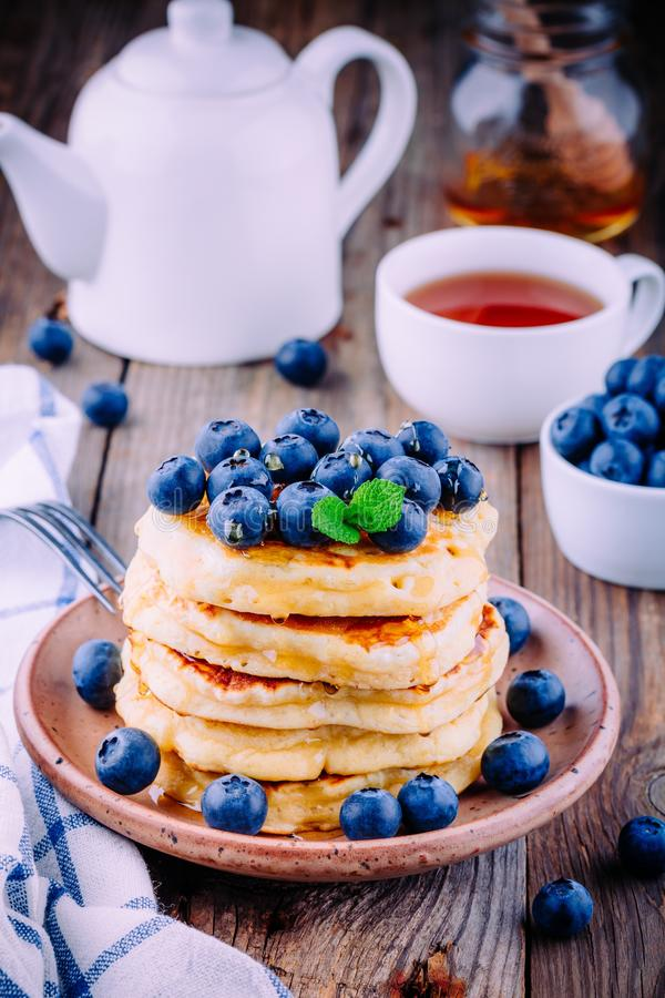 可口薄煎饼用新鲜的蓝莓和蜂蜜 库存照片