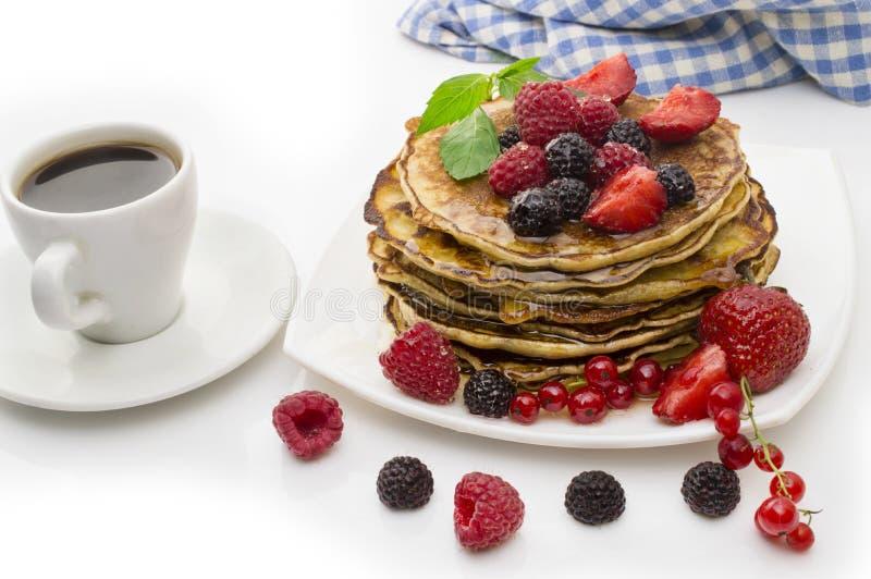 可口薄煎饼用莓果和枫蜜在白色背景 免版税图库摄影