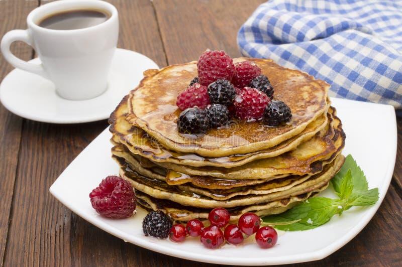 可口薄煎饼用莓果和枫蜜 顶层 图库摄影