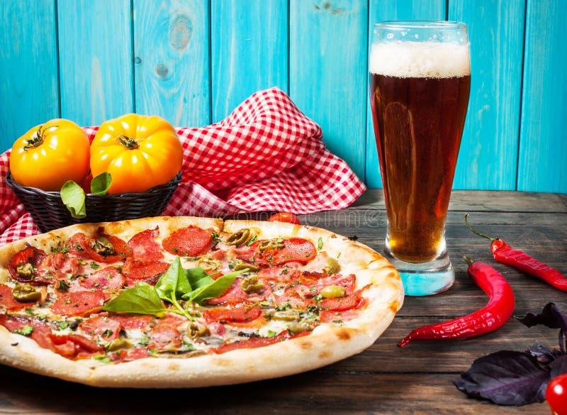 可口薄饼、在木桌上的杯啤酒菜和香料 库存图片