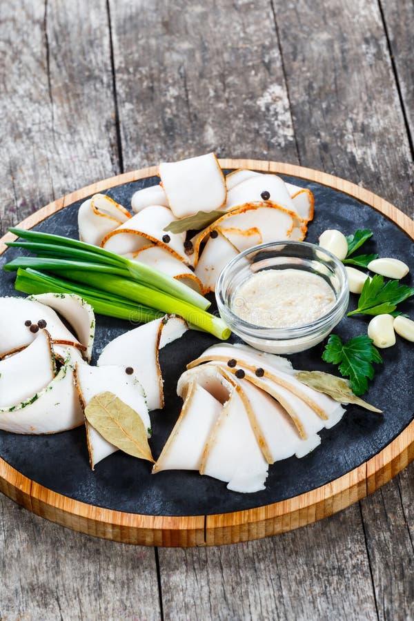 可口被切的猪肉油脂用香料、葱、大蒜和调味汁在切板在木背景关闭 免版税库存图片