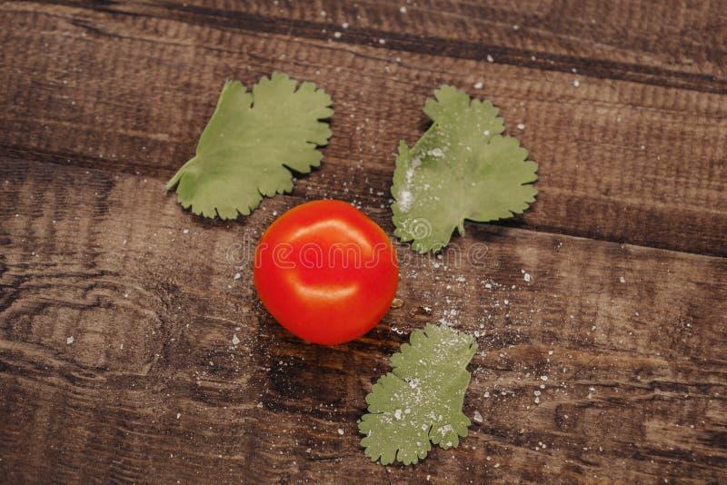 可口西红柿洒与在木背景的盐 库存照片