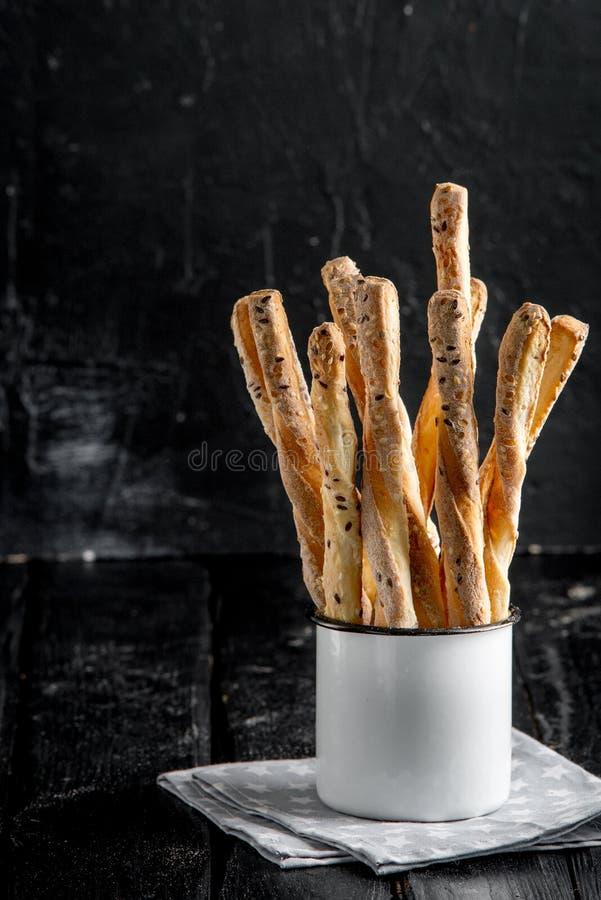 可口面包棒grissini 意大利语的开胃菜 在金属老式杯子的木黑暗的背景 图库摄影