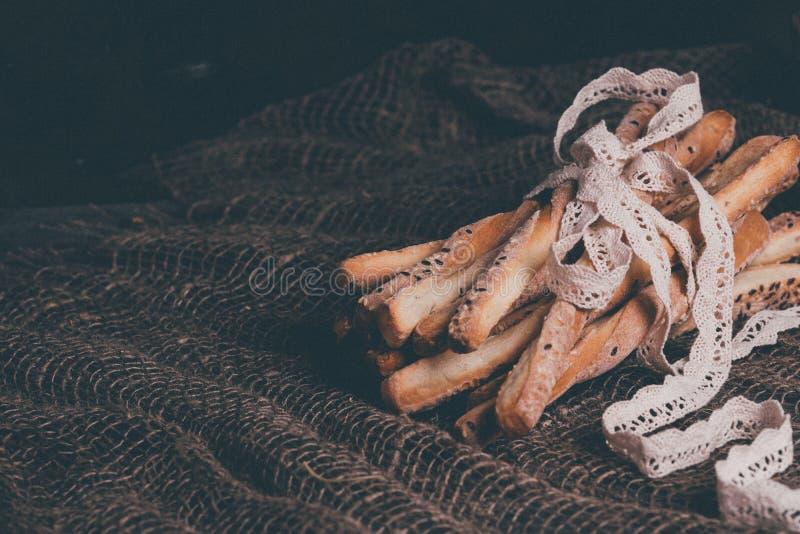 可口面包棒grissini 意大利语的开胃菜 木黑暗的背景和粗麻布和自然亚麻制鞋带 免版税库存图片