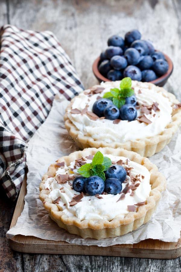 可口馅饼用在木桌上的奶油色和新鲜的蓝莓 库存照片