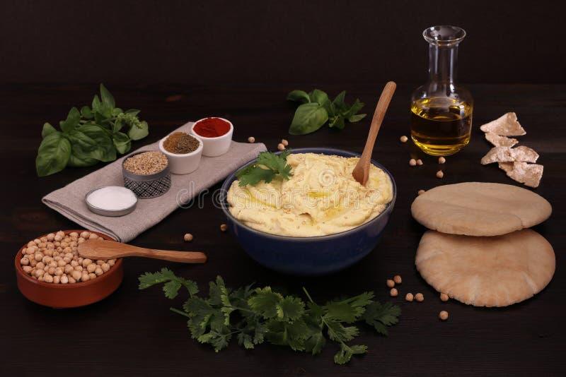 可口鸡豆HUMMUS用皮塔饼面包、荞麦面包、橄榄油和其他成份 免版税库存照片