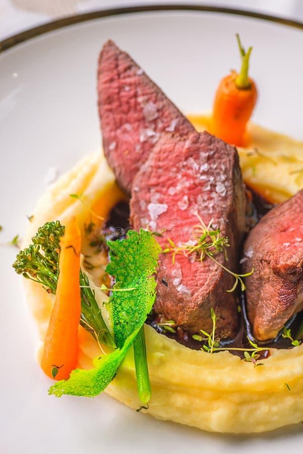 可口鹿肉牛排用在白色板材,专属餐馆的产品摄影的土豆饲料和菜 免版税库存图片