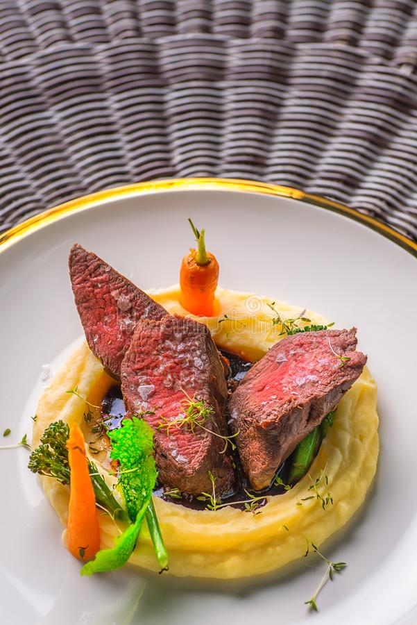 可口鹿肉牛排用在白色板材,专属餐馆的产品摄影的土豆饲料和菜 免版税库存照片