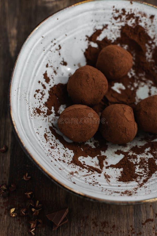 可口黑暗的巧克力糖块菌用在黑暗的背景,顶视图的四川胡椒 图库摄影