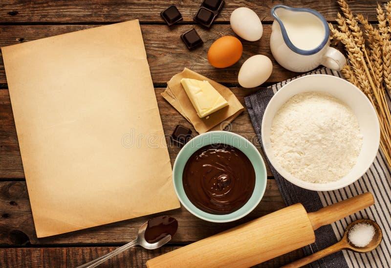 可可浆蛋糕-成份和白纸-背景 免版税库存照片