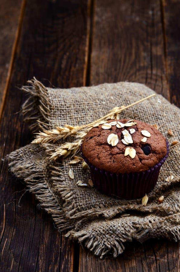 可可粉和巧克力片松饼在麻袋布 库存图片