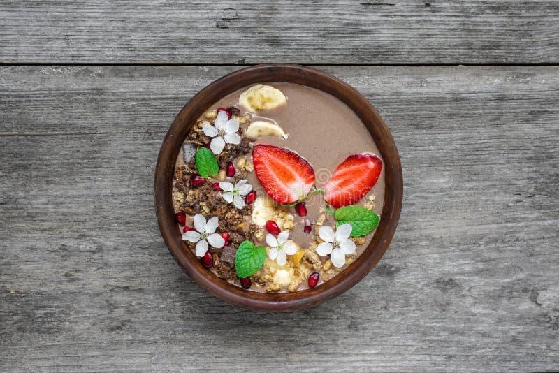 可可粉香蕉蛋白质有巧克力格兰诺拉麦片、草莓和用花装饰的石榴种子的圆滑的人碗 免版税库存图片