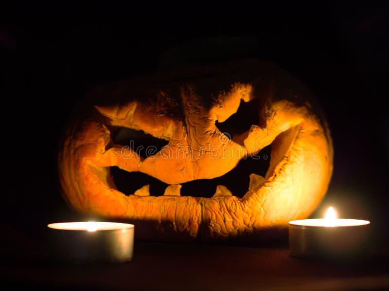 可怕万圣夜南瓜和灼烧的蜡烛在黑背景 免版税库存图片