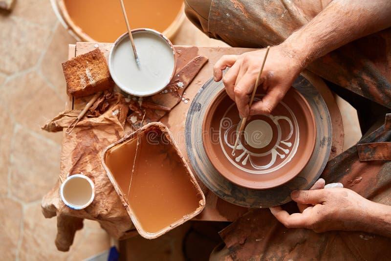可怕在一个木架子的面孔象手工制造陶瓷工杯子,特写镜头, shellow景深 库存图片