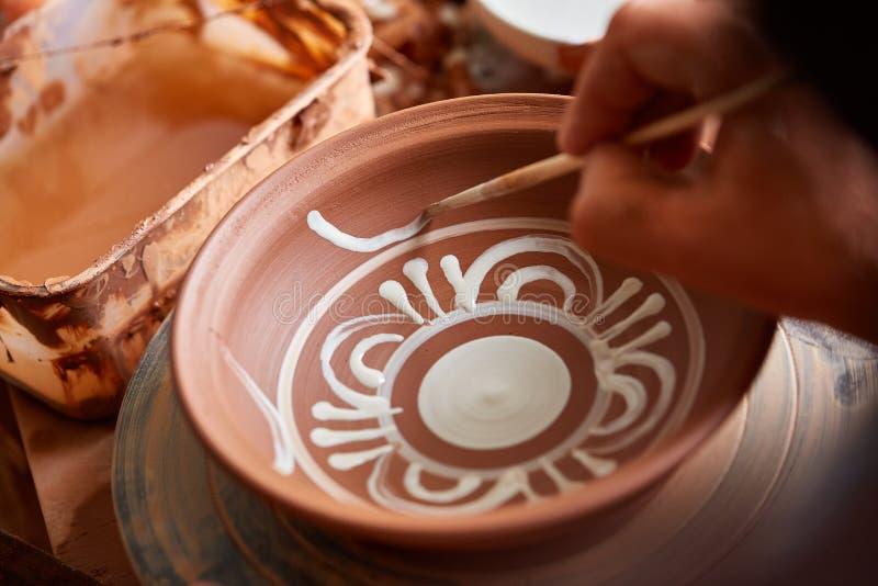 可怕在一个木架子的面孔象手工制造陶瓷工杯子,特写镜头, shellow景深 库存照片