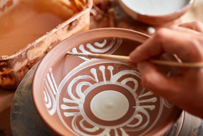 可怕在一个木架子的面孔象手工制造陶瓷工杯子,特写镜头, shellow景深 免版税库存照片