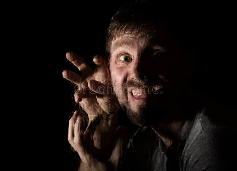 可怕有胡子的人黑暗的画象有假笑的,表现出不同的情感 水滴在玻璃、手和男性的 免版税库存图片
