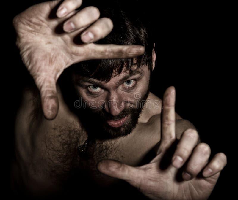 可怕邪恶的阴险有胡子的人黑暗的画象有假笑的,做签字与您的手指 有a的奇怪的俄国人 图库摄影