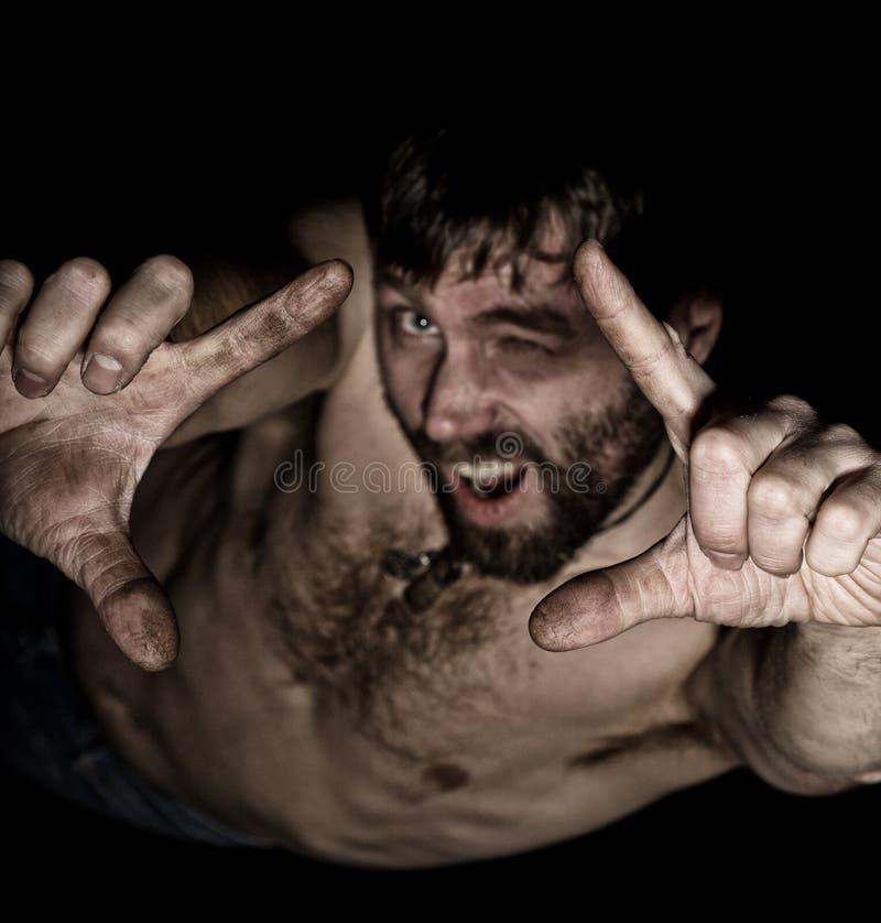 可怕邪恶的阴险有胡子的人黑暗的画象有假笑的,做签字与您的手指 有a的奇怪的俄国人 库存照片