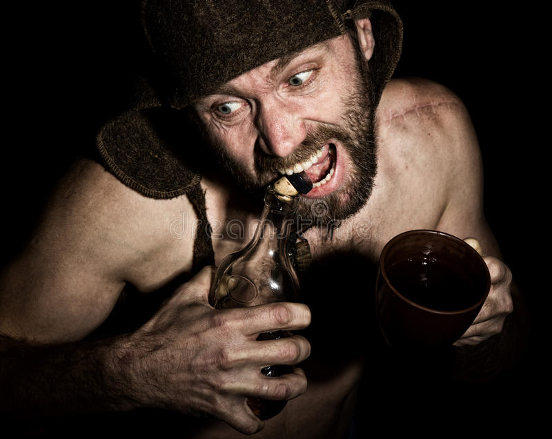 可怕邪恶的阴险有胡子的人黑暗的画象有假笑的,他打开一个瓶白兰地酒他的牙 奇怪的俄国人 图库摄影