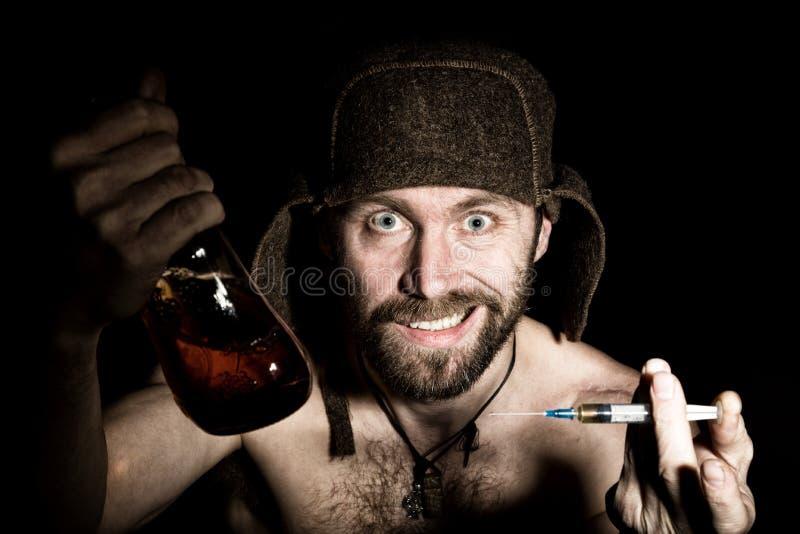 可怕邪恶的阴险有胡子的人黑暗的画象有假笑、提议各种各样的药物,注射器或者一个瓶的科涅克白兰地 库存图片