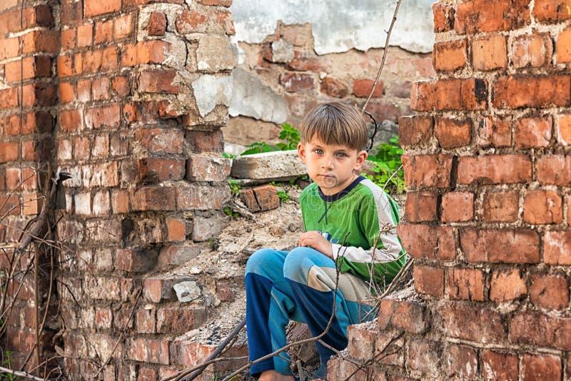 可怜和不快乐的孤儿男孩,坐一个被毁坏的大厦的废墟和废墟 演出的照片 库存图片