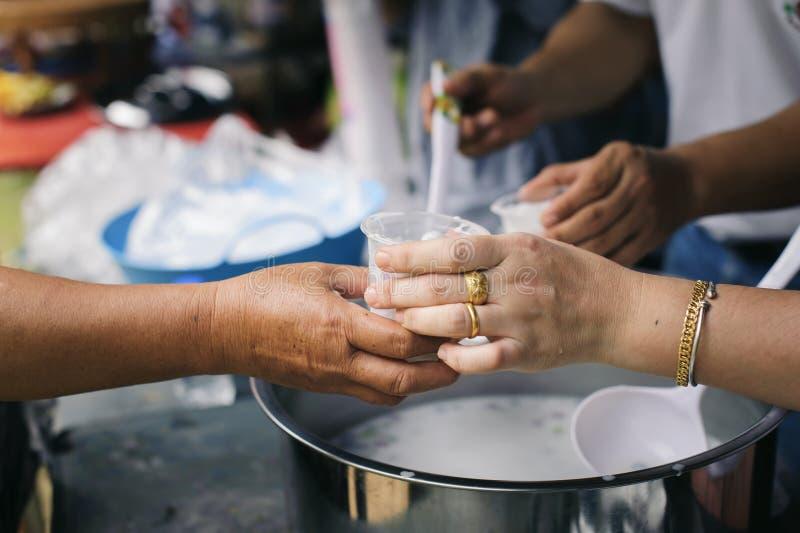 可怜和无家可归的人的免费食物捐赠食物对食物较少人:贫寒分享从更加亲切的社会的食物 免版税库存照片