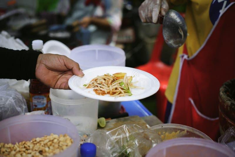 可怜和无家可归的人的免费食物捐赠食物对食物较少人:贫寒分享从更加亲切的社会的食物 库存照片