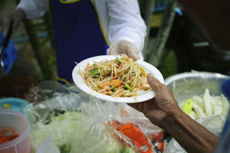 可怜和无家可归的人的免费食物捐赠食物对食物较少人:贫寒分享从更加亲切的社会的食物 库存图片