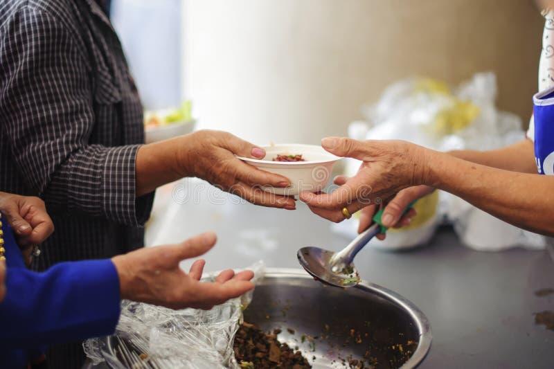可怜的人民从捐款人接受捐赠的食物,展示相互分享在今天社会:叫化子乞求从捐款人的食物 免版税库存图片